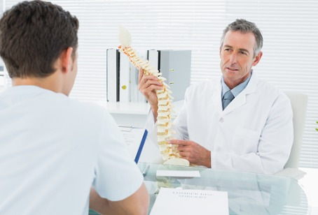 A Chiropractor in Hinsdale IL showing a patient a model of a spine