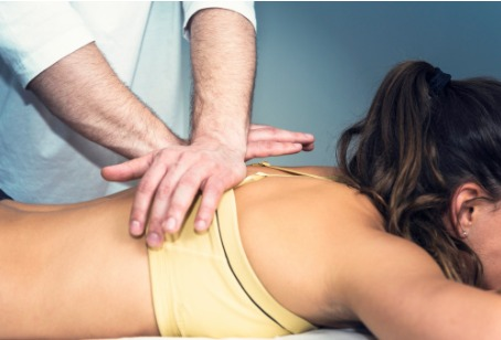 A Chiropractor for Oak Brook IL making spinal adjustments to a patient's back