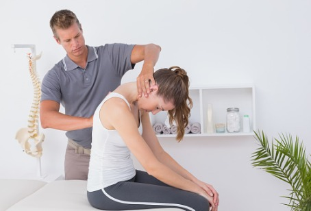 A chiropractor making adjustments to a woman's spine, as a part of Integrative Medicine in Westmont IL