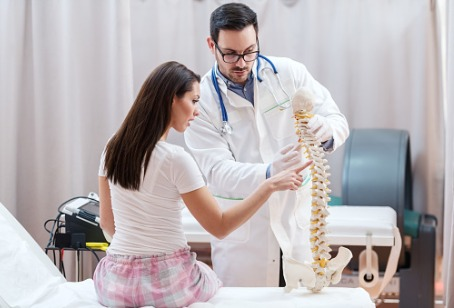 A Chiropractor in Willowbrook IL showing a patient a model of a spine