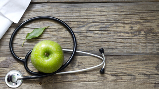 Apple and stethoscope representing Natural Medicine Doctor in Clarendon Hills IL