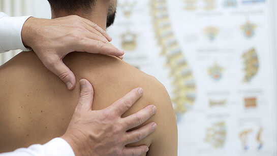A chiropractor Downers Grove IL performing chiropractic care on a young adult